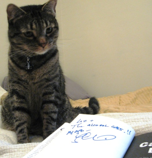 "Smirnoff checking out his signed copy of ""Cat Daddy."""